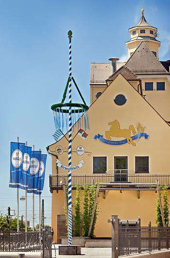 Hier ist ein Foto des Brauhaus Riegele mit Maibaum im Vordergrund