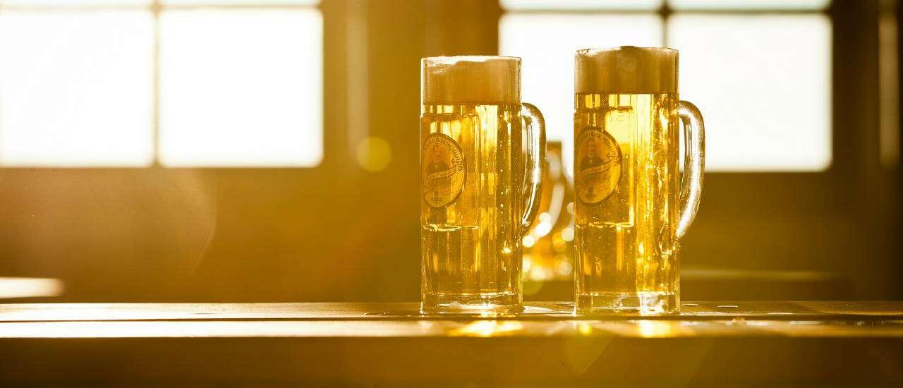 Hier ist ein atmosphärisches Bild von zwei Bierkrügen im Gegenlicht