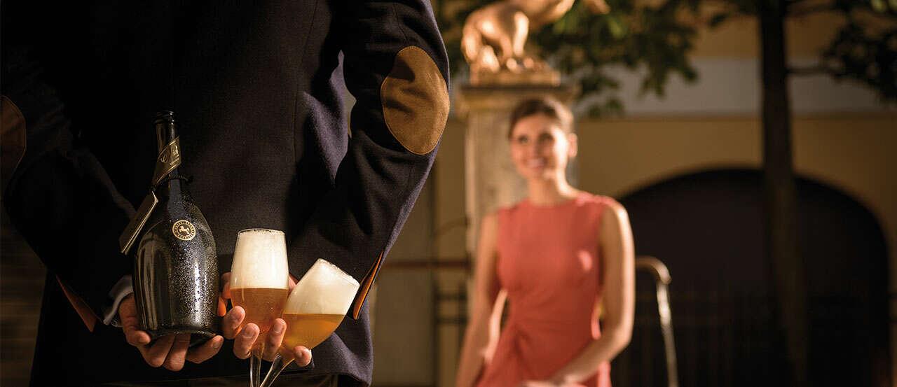 Hier ist ein atmosphärisches Bild, dass einen Mann von hinten zeigt, der für eine Frau mit einer Flasche Michaeli überraschen möchte